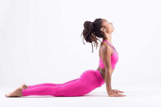 Pretty young black woman doing yoga exercise isolated on white background