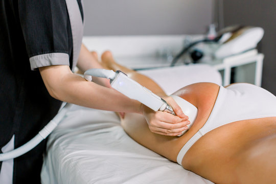 Female doctor cosmetologist doing roller massage with apparatus on female client thighs, close up. Roller massage in medical spa center