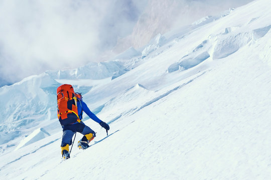 Climber reaches the summit of mountain peak enjoying the landscape view. Everest, Nepal