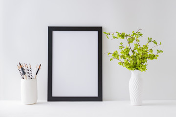 Home interior with decor elements. Mockup with a black frame, branches with green leaves on a light background