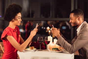 Couple Using Cellphones Texting During Romantic Dinner In Fancy Restaurant