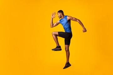 Handsome black sportsman walks highly lifting knees Wall mural