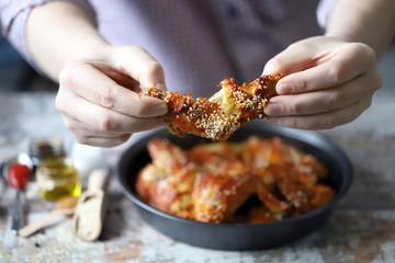 In de dag Buffel Selective focus. A man eats buffalo wings. Buffalo chicken wings in tomato chili sauce.