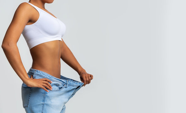 Cropped of young woman with too large jeans