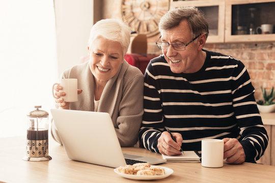 Cheerful senior couple watching news on laptop online at kitchen