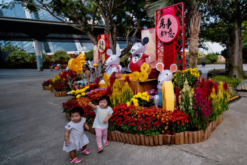Young girls react as they pose for a photo beside sculptures of rats on display to celebrate the upcoming Lunar Year of the Rat at Singapore's Gardens by the Bay