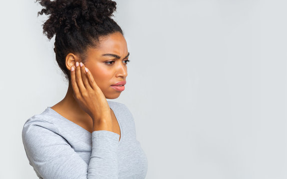 Afro girl suffering from otitis, rubbing her inflamated ear