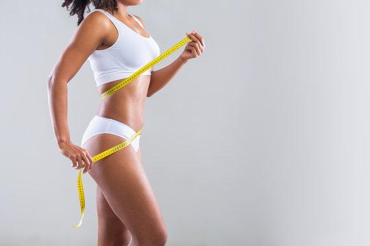 Afro girl in white underwear measuring her body