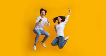 Overjoyed multiracial couple jumping in the air and celebrating success