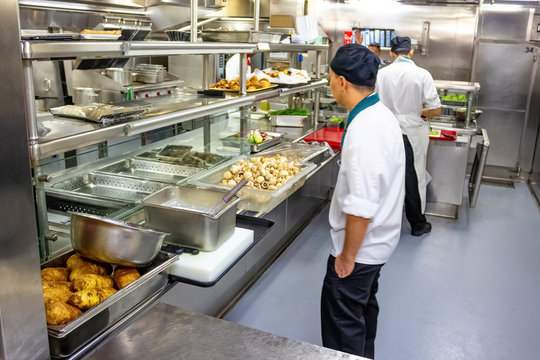 Kitchen crew work in the galley of a cruise ship in the Caribbean Sea