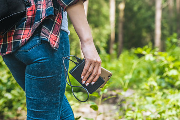 Power bank in a girl s hand, against the background of the forest and greenery.