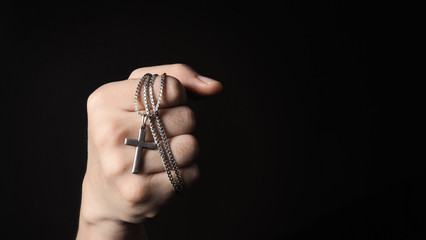 Close-up images of crucifix pendant and necklace in hand on black color background in studio which represent praying for god or jesus and thank gods for giving peaceful and faithful to people