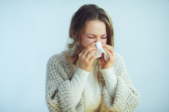 woman with napkin sneezing against winter light blue background