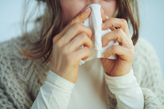 Closeup on ill elegant woman wiping nose with napkin
