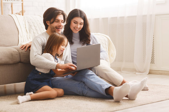 Happy family with daughter using laptop together at home