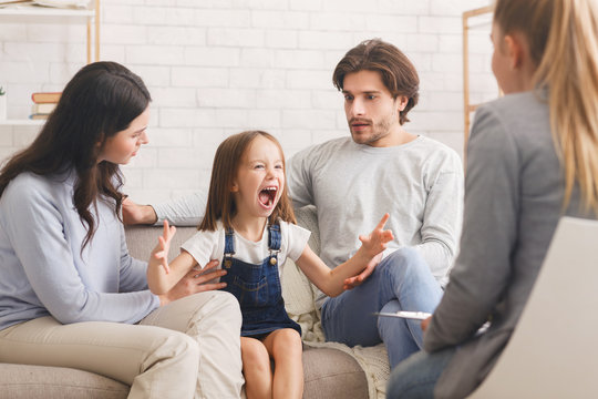 Shocked parents soothing their screaming little daughter at psychologist consultation