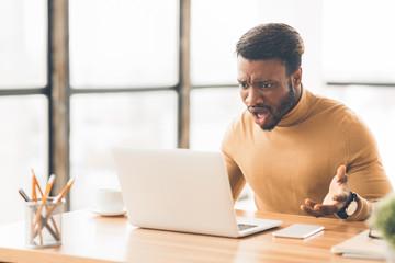 Shocked surprised balck guy using pc at work