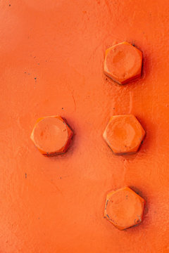 Background: orange metal background with orange painted screws