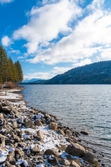 The Donner lake under the snow in winter, in the Nevada, with chalets on the beach