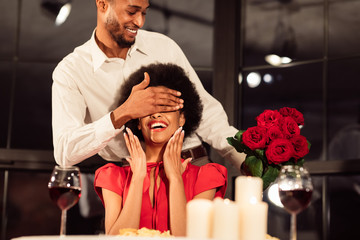 Man Covering Woman's Eyes Holding Bouquet Celebrating Valentine In Restaurant