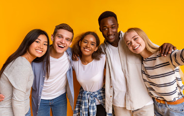 Friendly international students taking selfie over yellow background