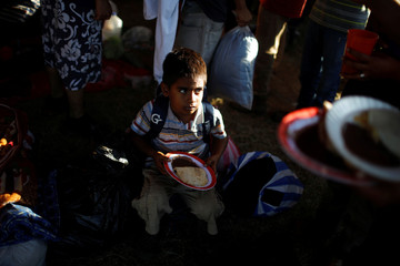 A migrant child travelling to the U.S. east his breakfast in an improvised shelter in Tecun Uman
