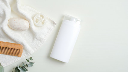 Hair care product design concept. SPA cosmetic bottle packaging, wooden hair comb, white towel, organic soap, luffa sponge on green background. Minimalist cosmetic product mockup, natural branding