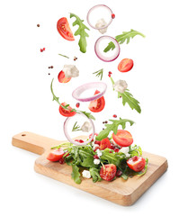 Board with tasty salad and falling ingredients on white background