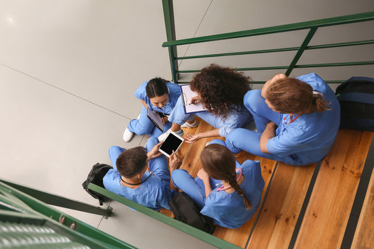 Group of medical students on stairs in modern clinic, top view