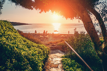 Cyprus landscape. Descent along paved path to beach and sea at sunset. Mediterranean vacation concept.