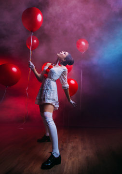 Happy funny sexy joy Woman clown in old costume knee high black retro boots, creative art bright mad makeup face, hairstyle two bun. Backdrop black gothic mystic room fog smoke, hold red balloon.