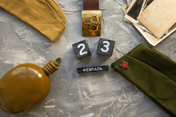 "Flask, cap, soldier is military belt, old photographs of the war years and a wooden calendar with the date February 23. Fatherland defender day.  Text in Russian ""February 23."