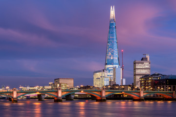 View of London city skyline on colorful sunset, with Southwark bridge over Thames river and the Shard skyscraper in the middle of the frame