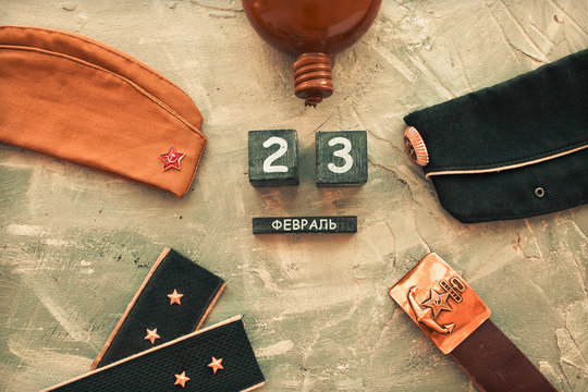 Flask, cap, soldier's military belt,shoulder straps  of the war years and a wooden calendar with the date February 23. Fatherland defender day.