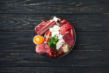 Dog food. Natural Organic Raw meat and dairy products, fish, egg, vegetables and supplements. Black wooden background. Close up. Papier Peint