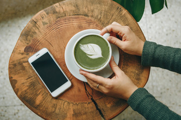 Fototapeten Tee View from above. Girl holds in her hand a cup with fragrant fresh and healthy green matcha latte tea on a wooden table. Nearby lies a cell phone.