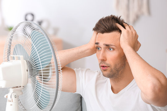 Shocked man near electric fan at home