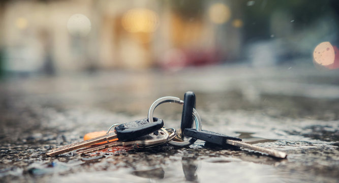 Set of lost keys on the ring on wet ground on the street