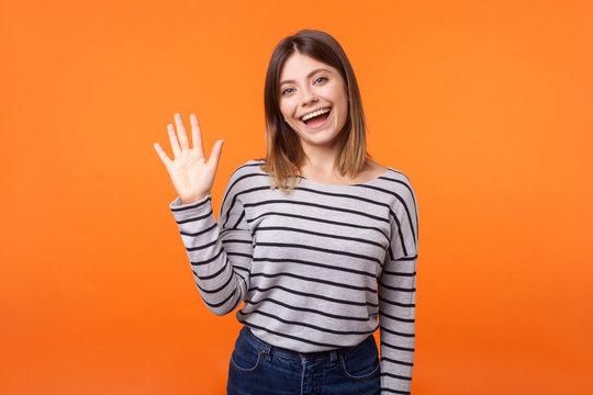 Hello! Portrait of adorable friendly woman with brown hair in long sleeve shirt standing waving hand, looking at camera with engaging toothy smile. indoor studio shot isolated on orange background