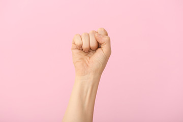 Hand of woman with clenched fist on color background