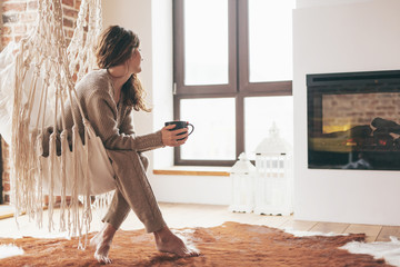 Woman wearing cashmere nightwear relaxing in cabin near fireplace