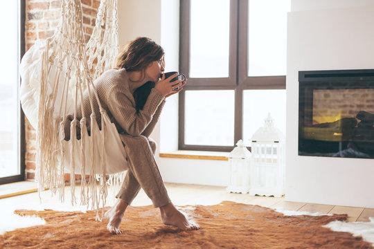 Woman wearing cashmere nightwear relaxing in cabin near fireplace