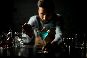 Foto auf Leinwand Alkohol Professional bartender deacorating a blue alcoholic cocktail in a martini glass with a spikelet with twezzers