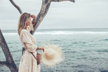 Acrylic Prints Akt Boho model wearing dress and straw hat on the beach