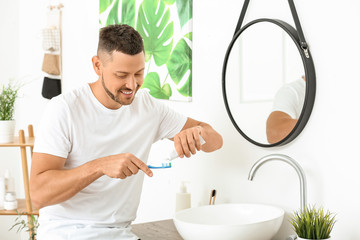 Fotomurales - Handsome man brushing teeth at home