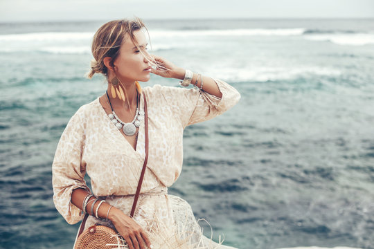 Boho model wearing dress and straw hat on the beach