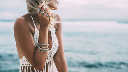 Boho model wearing crochet top and silver jewelry on the beach