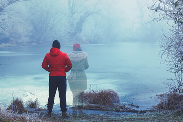 Obraz Lonely man in red jacket standing by the lake in winter, with transparent woman figure standing next to him - fototapety do salonu