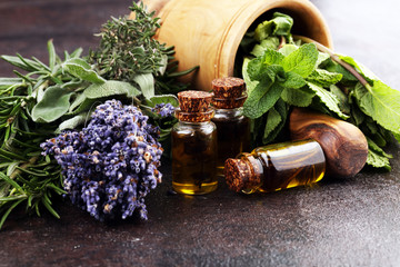 Fresh herbs from the garden and the different types of oils for massage and aromatherapy on table...
