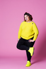 Cheerful plus size model in casual clothes, fat woman in black jeans and yellow jumper on pink background